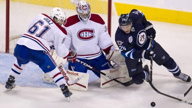 Montreal Canadiens goaltender Carey Price (31) and P.K. Subban (76) try to keep the loose puck from Winnipeg Jets' Bryan Little (18) during the second period Thursday.