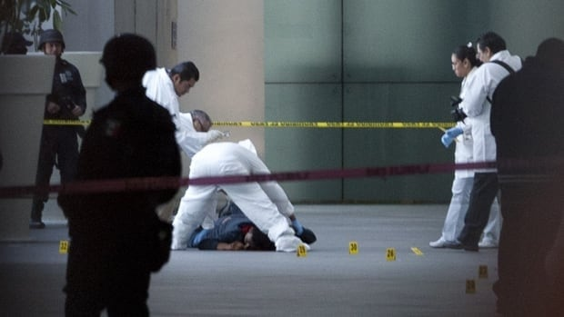 A forensic team inspects a body at Mexico City's international airport after men opened fire, killing three federal policemen on an anti-drug mission.