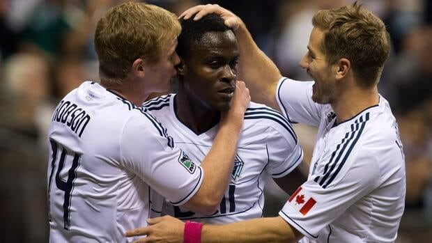 Whitecaps midfielder Gershon Koffie, centre, celebrates his goal against Chivas USA with teammates Barry Robson, left, and Jordan Harvey on Wednesday.
