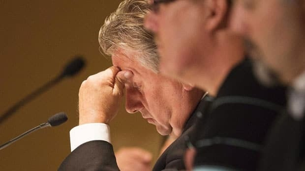 Canadian Auto Workers union president Ken Lewenza rubs his forehead as he takes questions from the media following a meeting to discuss contracts with General Motors in Toronto on Aug. 14.