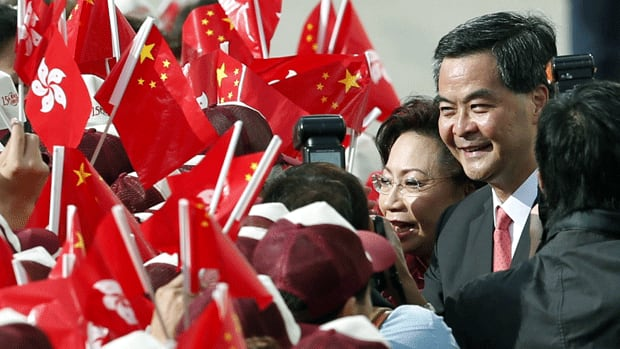 Chief Executive Leung Chun-ying holds up copies of his inaugural policy address delivered Wednesday that emphasized measures aimed at solving Hong Kong's housing crisis.