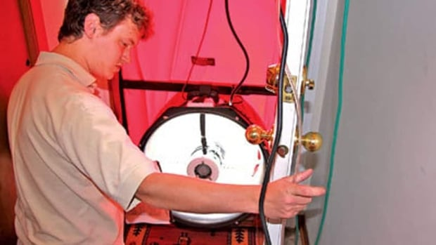 An energy auditor uses a blower door fan to de-pressurize house to identify air leaks and cracks.