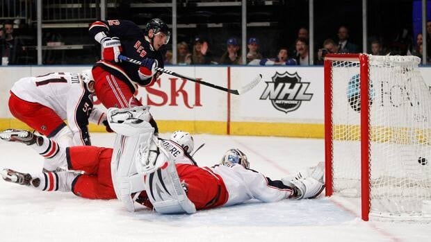 Team doctors and emergency personnel tend to Columbus Blue Jackets centre Artem Anisimov after being hit Thursday by Red Wings defenceman Kyle Quincy.