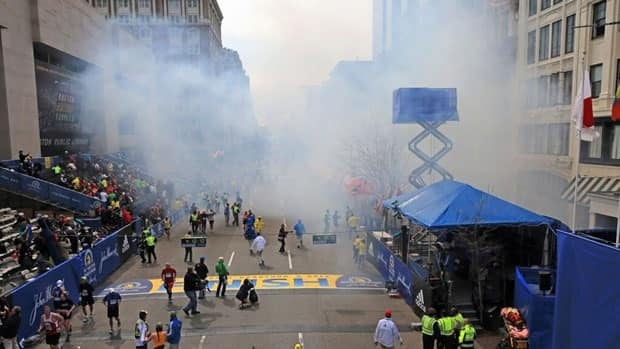 Medical workers aid injured people at the Boston Marathon following an explosion.