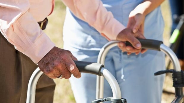 A man uses a walker with help from a caregiver. Join CBC KW's video chat on health care in Waterloo Region.