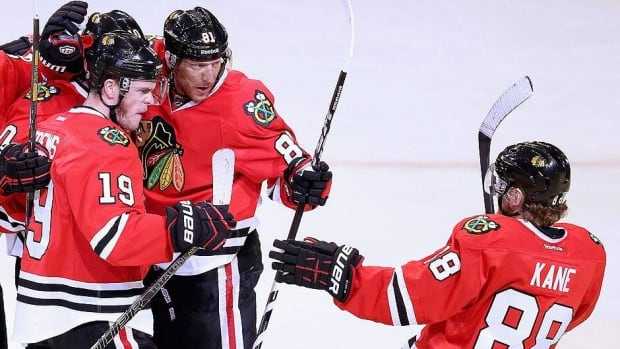 The Blackhawks' Jonathan Toews, left, gets his stick up on the Red Wings' Jonathan Ericsson during Thursday night's Game 4 in Detroit but wasn't penalized on the play. However, a clearly frustrated Toews did take two high-sticking penalties in the second period along with a hooking minor.