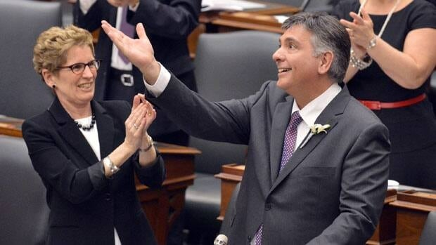Ontario Premier Kathleen Wynne applauds Finance Minister Charles Sousa as he begins to deliver his first budget speech.