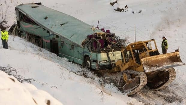 A bulldozer strains to pull the crashed bus out of the gully it careened into Dec. 30
