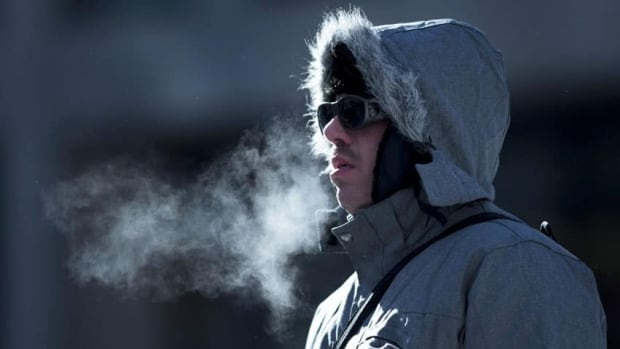 A man waits for the bus, braving temperatures which felt like -40C with windchill in Ottawa on Wednesday.