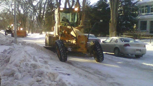 A snow-clearing crew clears a street in Winnipeg's Fort Rouge neighbourhood on Wednesday, going around parked cars.