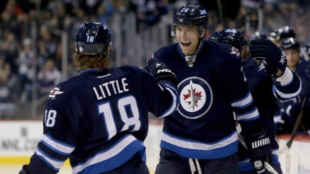 Winnipeg Jets forwards Andrew Ladd (16), Bryan Little (18), and defenceman Zach Bogosian (44) celebrate after Ladd opened the scoring against the Tampa Bay Lightning in Winnipeg on Tuesday.