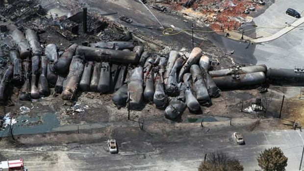 Aerial view of charred freight train that devasted Lac-Mégantic, Que. Moody's predicts it will lead to higher costs for shipping oil by rail.