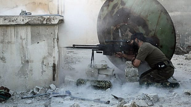 A rebel fighter with the Free Syrian Army shoots back at a sniper during clashes with pro-government forces in Aleppo's Karm al-Jabal district on June 3, 2013.