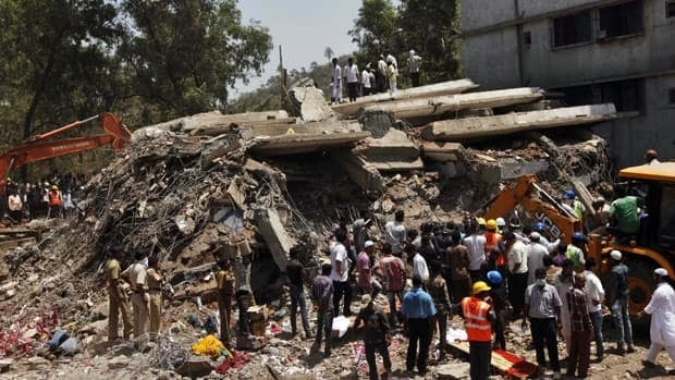 People gather near debris at the site of the collapsed building on the outskirts of Mumbai on Friday.