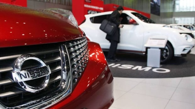 A visitor inspects a Nissan SUV at a gallery inside the headquarters of Nissan Motor Co. in Yokohama, Japan.  The company said Wednesday it is cutting prices on seven of its 18 models in the U.S.