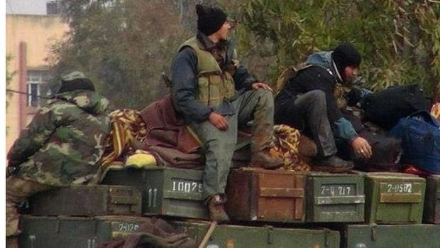Rebels from al-Qaeda affiliated Jabhat al-Nusra, as they sit on a truck full of ammunition, at Taftanaz air base, that was captured by the rebels, in Idlib province in early January.