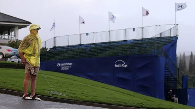 A course volunteer stands in the high winds during a weather delay before the replay of the first round of the Tournament of Champions at the Plantation Course on Saturday in Kapalua, Hawaii.