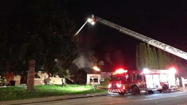 Maple Ridge fire crews battle a two-house blaze in the 22100 block of Lougheed Highway early Friday morning.