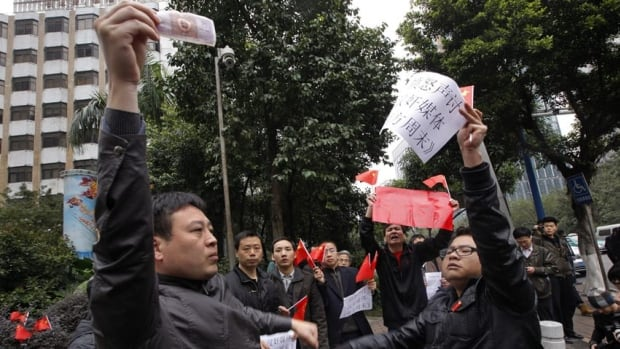 A supporter of the Southern Weekly newspaper, left, confronts with leftist as the latter stage a counter-protest outside the headquarters of the newspaper in Guangzhou on Wednesday.