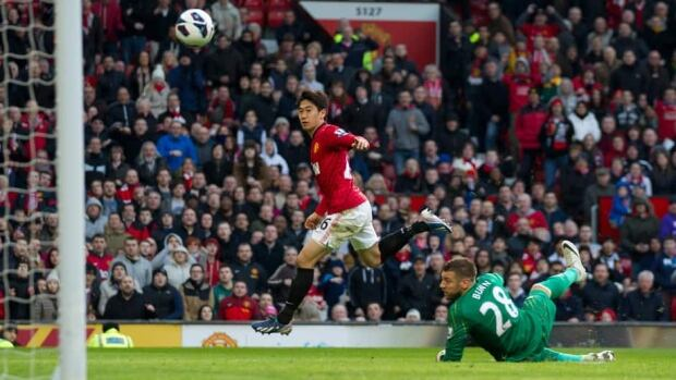 Manchester United's Shinji Kagawa, centre, scores past Norwich's goalkeeper Mark Bunn at Old Trafford Stadium in Manchester, England on Saturday.