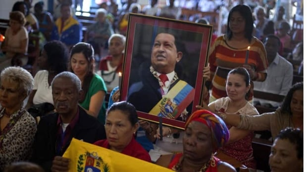 Venezuelan embassy workers in Cuba hold up a framed image of ailing President Hugo Chavez during a monthly Catholic service devoted to the sick. Chavez underwent his fourth cancer surgery in Cuba in December and hasn't spoken publicly in a month.