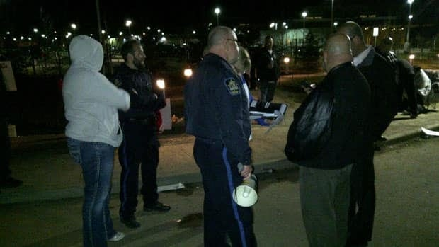 Guards stand outside the Edmonton Remand Centre on Friday night.