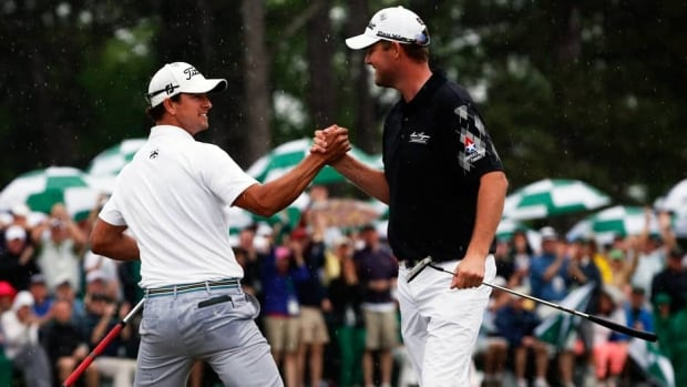 Adam Scott of Australia, left, is congratulated by compatriot Marc Leishman after sinking a birdie putt on the 18th green during final round play in the 2013 Masters golf tournament at the Augusta National Golf Club.