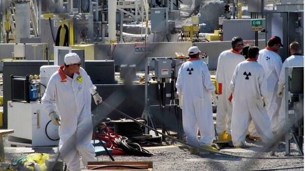 Workers at the Hanford nuclear site work around a tank farm. Six underground radioactive waste tanks at the nation's most contaminated nuclear site are reported to be leaking.