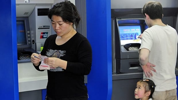 A child watches her parents take money out of an automated bank machine. Visa says young people tend to overshare sensitive financial information.