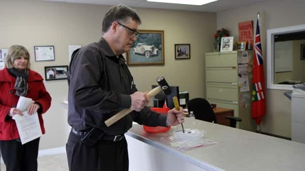Hamilton East-Stoney Creek MPP Paul Miller chisels away at an ice block that represents the provincial freeze on minimum wage.
