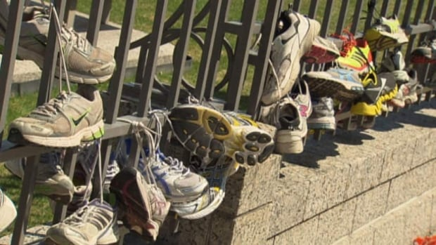 Ottawa runners tied running shoes to a fence surrounding the U.S. Embassy on Monday after a memorial walk for the Boston Marathon bombing victims.