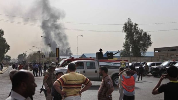 Black smoke from a car bomb attack is seen in Baghdad Thursday, part of a string of attacks that killed 24 and wounded 57 less than a week before the 10th anniversary of the U.S.-led invasion of Iraq.
