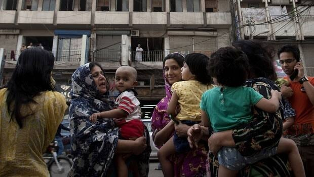 People evacuate buildings and gather on a road as a tremor of an earthquake was felt in Karachi, Pakistan, on Tuesday. Dozens were reportedly killed in the latest earthquake to hit the region.