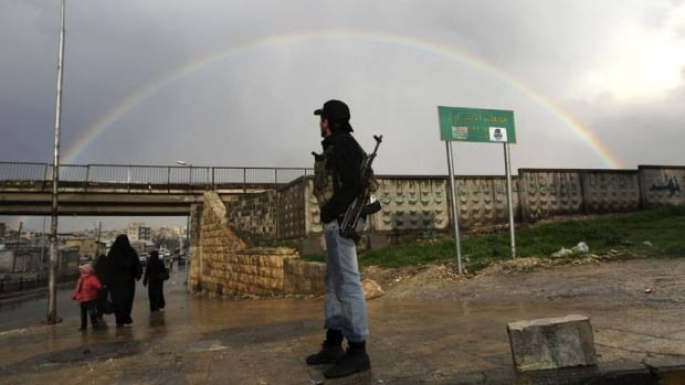 A member of the Free Syrian Army stands with his weapon as he looks at a rainbow. The country's electricity minister told the state news agency that technical teams were working around the clock to restore power in the south.