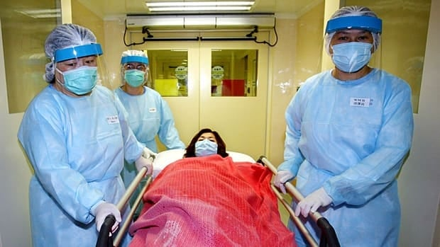 Health care workers wheel a fake patient through the halls of a Hong Kong hospital during a pandemic preparedness drill in 2004. Drills are one of many measures introduced in the wake of SARS, a virus that devastated the city a decade ago.