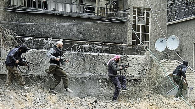 Free Syrian Army fighters take up positions in the rubbled Damascus suburb of Sidi Meqdad earlier this week.