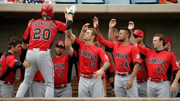 Canada's Michael Saunders is congratulated in the dugout after hitting a home run against the Milwaukee Brewers Tuesday, March 5, 2013, in Phoenix.