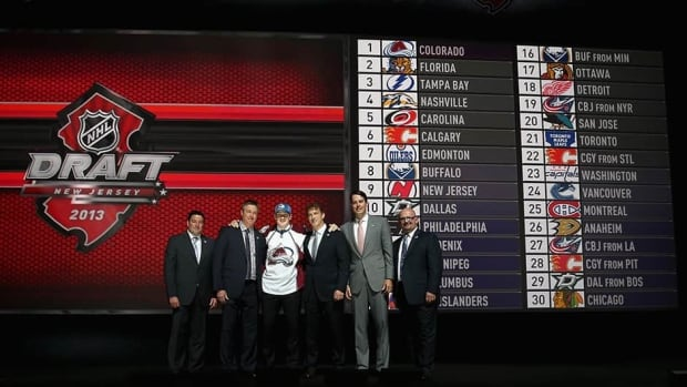 Nathan Mackinnon, centre, poses with head coach Patrick Roy, second left, and executive vice president of hockey operations Joe Sakic, second right, after being selected first overall in the NHL draft by the Colorado Avalanche on Sunday.