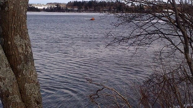 Three volunteer firefighters in cold water survival suits launched a boat into the river for the rescue.