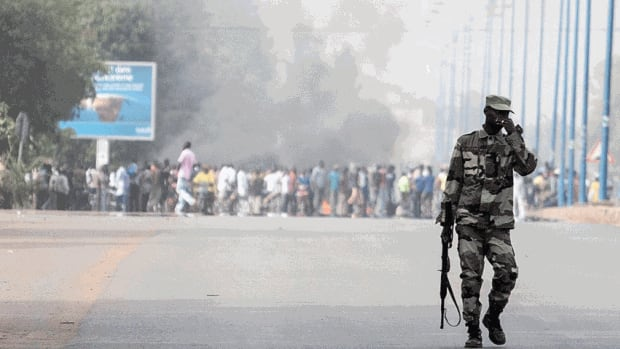 A soldier patrols near a burning road block outside the paratrooper camp in Bamako, Mali. The first known suicide bombing since France started its military intervention on Jan. 11 occured in Gao on Friday. Only the bomber died.