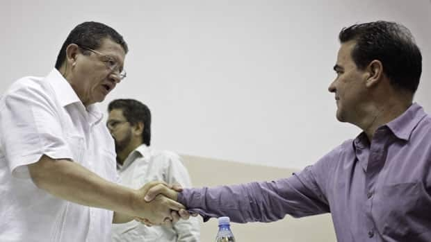 FARC negotiator Pablo Catatumbo. left, shakes hands with Colombia's government negotiator Frank Pearl during a conference in Havana, Sunday.