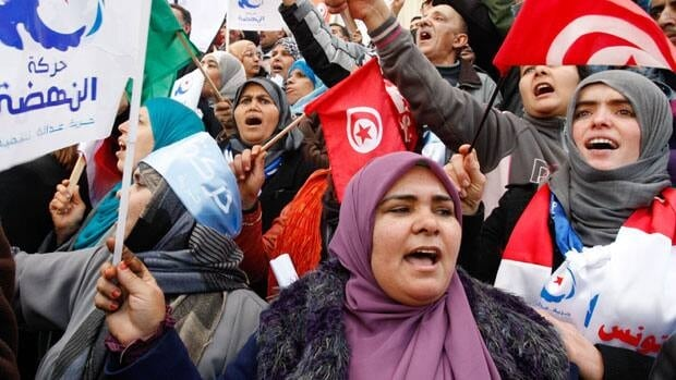 Supporter of the Islamist ruling party Ennahda, hold Tunisian and party flags during a rally in Tunis, Tunisia, Saturday, Feb. 16, 2013.