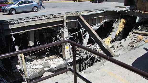 A man leans on a column next to the collapsed roof of the Algo Centre Mall in Elliot Lake, Ont. on Saturday June 23, 2012.