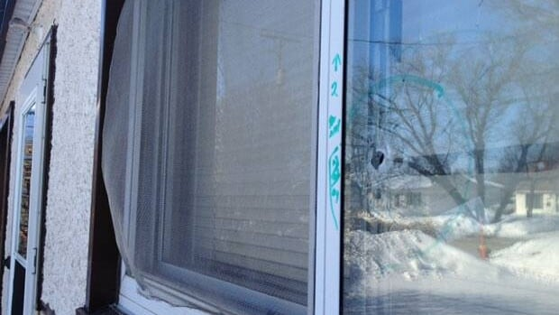 Visible bullet hole in a window of a home which Winnipeg police say was shot at Friday night.