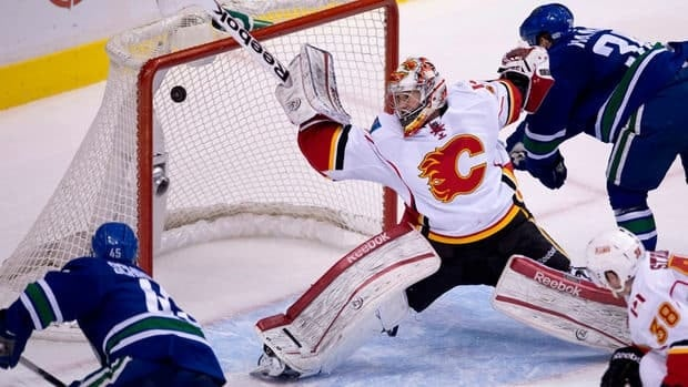 Vancouver Canucks forward Jordan Schroeder, left, scored his second goal Saturday night on Calgary Flames goalie Leland Irving, centre, at Rogers Arena.