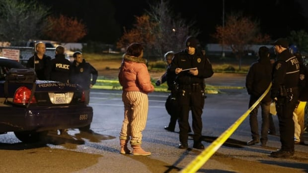 Police officers interview a woman who told reporters she heard gunshots at the scene of an overnight shooting that left five people dead at an apartment complex in Federal Way, Wash.