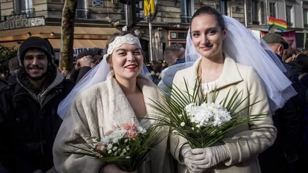 Women pose during a demonstration for the government project to legalize same-sex marriage and adoption for same-sex couples in Paris on Jan. 27.