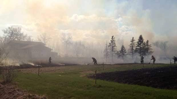 Firefighters battle a grass fire amid smoky conditions on Fraser Road in south Winnipeg on Wednesday afternoon.