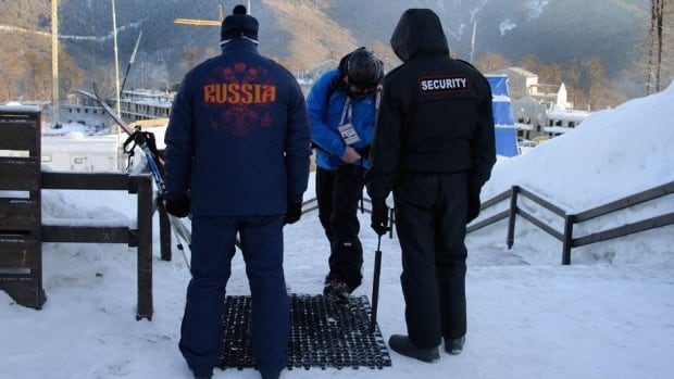 Security personnel check a visitor entering the gondolas at the Rosa Khutor Mountain Resort, site of the alpine skiing events for the 2014 Sochi Olympics.