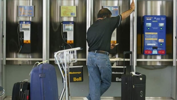 A traveller talks on a payphone at Pearson International Airport in Toronto. Payphones are disappearing from public places and the CRTC wants to know what to do about it.